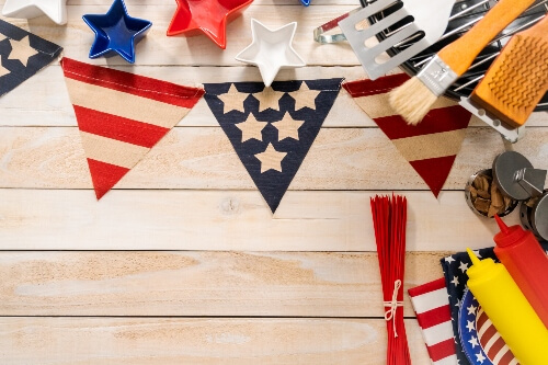 American flag decorations sit on a table next to ketchup, mustard, plates, and napkins.
