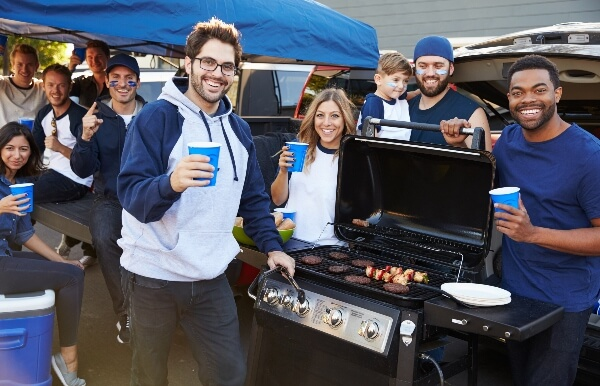 A group of friends get together to celebrate the game day with a bbq tailgate.